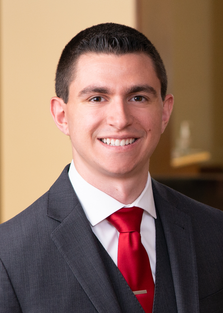Professional headshot of Ryan Boonstra in suit standing in an office