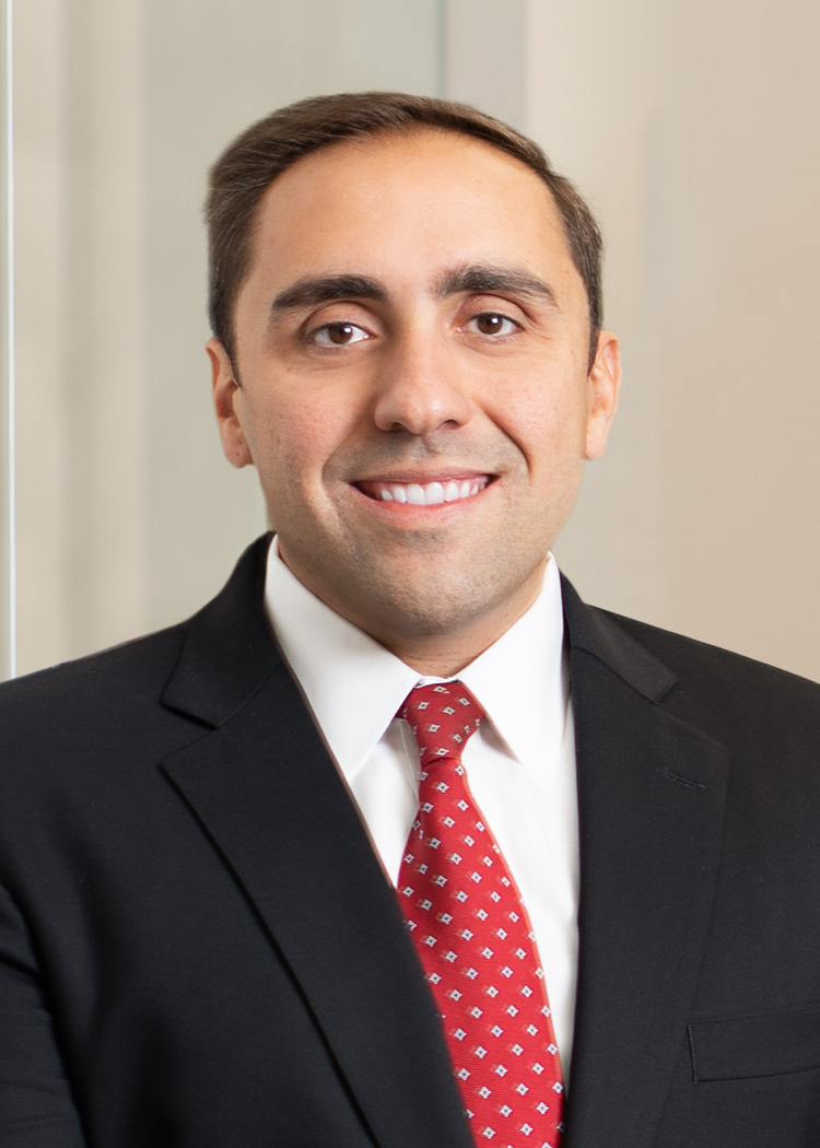 Professional head shot of Jeffrey Valacer in a suit standing in an office