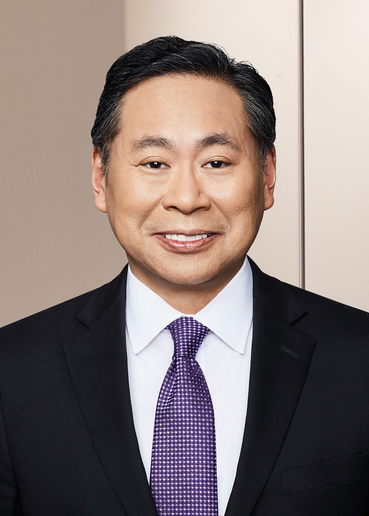Professional photo of Shanlon Wu in a suit standing in an office