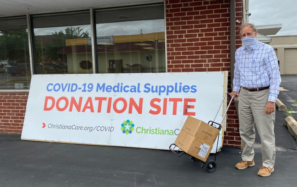 Jim Harker with a box standing in front of a donation site sign