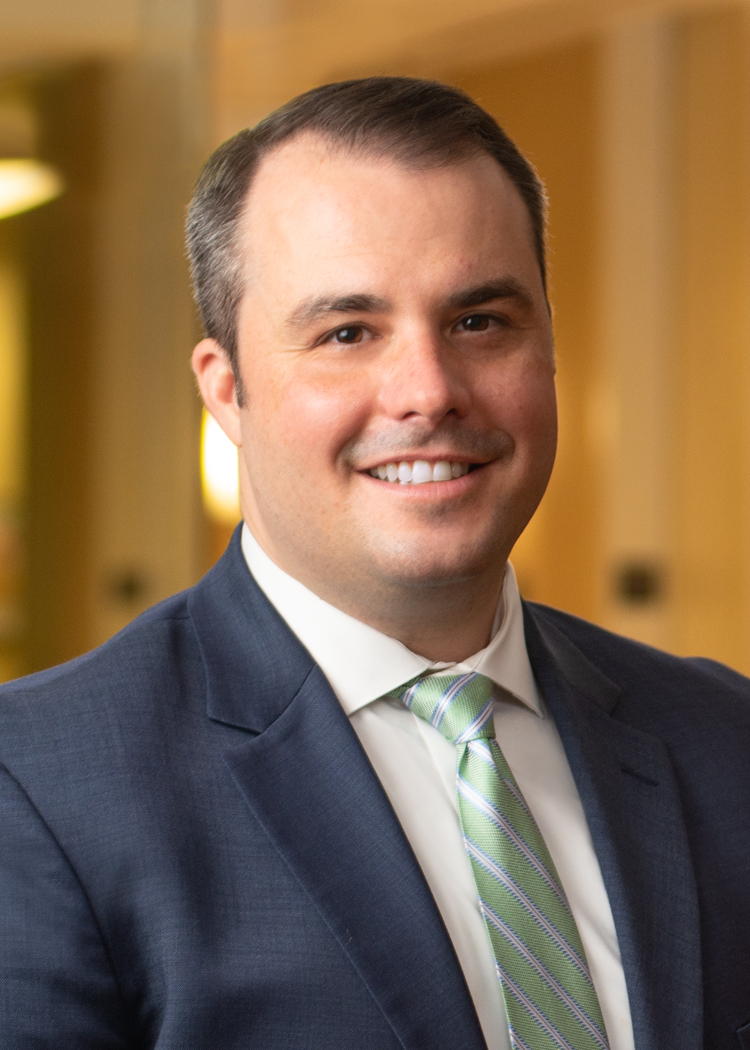 Professional photo of Anthony Chwastyk in a suit standing in an office